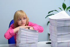 Girl in the office hopelessly looking at the stack of documents Stock Photos