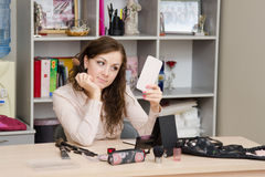Girl in office looks the mirror. Young woman sitting at office table, laid out on the table cosmetics Stock Images