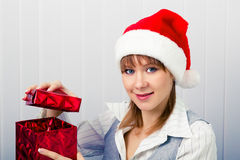 Girl in the office in Santa hats with a gift Royalty Free Stock Photos