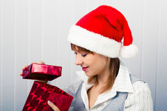 Girl in the office in Santa hats with a gift Royalty Free Stock Image