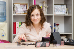Girl in office selects the appropriate brush for makeup Stock Images