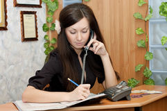 Girl at office speaking on phone Stock Image