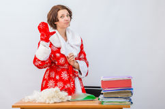 Girl office staff member dressed as Santa Claus waving his hand in a mitten at his desk Royalty Free Stock Images