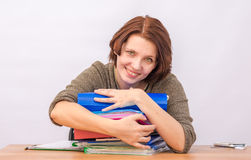 Girl office staff smiling hugging a stack of folders Stock Photo