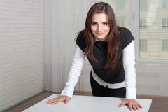 Girl in the office stands propped her hands on the table Stock Photos