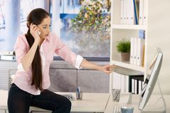 Girl in office talking on phone Royalty Free Stock Images