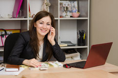 Girl and office talking on phone looking into frame smiling Royalty Free Stock Photography