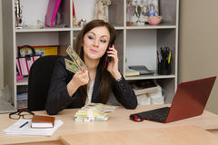 Girl a office talking on phone and looking at paper money in hand Stock Photo