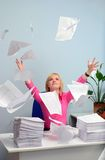 The girl at office throws a paper. The tired girl throws documents at office stock photo