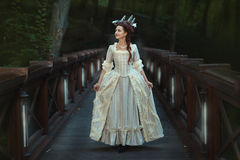 The girl in an old ball dress walking on bridge. Royalty Free Stock Photo