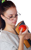 The girl with the old book and an apple Royalty Free Stock Images