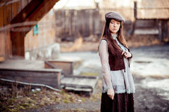 Girl in old fashioned outfit wearing flat cap at courtyard of wooden barracks, retro look. Stock Photos