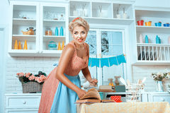 Girl in old-fashioned style, and stands  kitchen preparing meal. Stock Photography