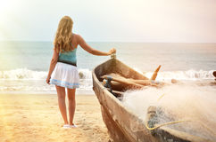 Girl at the old fishing boat looking to the ocean Stock Images