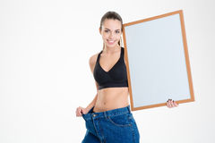 Girl in old jeans became too big holding blank board Royalty Free Stock Photos