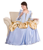 Girl in old  long blue  dress on armchair. Royalty Free Stock Image