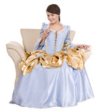 Girl in old long blue dress on armchair. Royalty Free Stock Photo
