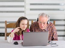 Girl and old man on laptop Stock Photos