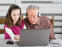 Girl and old man on laptop Royalty Free Stock Photography