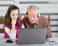 Girl and old man on laptop Royalty Free Stock Image