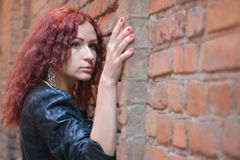 Girl on the old red brick wall. Fashion girl with red hair stands leaning against a old red brick wall background royalty free stock photos