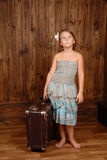 Girl with old shabby suitcase, thoughtfully looks up Stock Photo