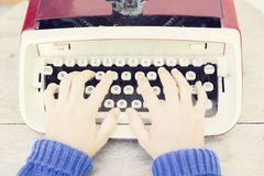 Girl with old style typewriter on the wooden table. Close up Royalty Free Stock Image