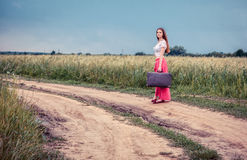 Girl with old suitcase on the road Royalty Free Stock Photos