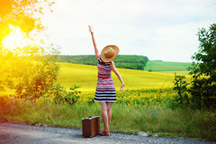 Girl with old suitcase standing on roadside in sun Royalty Free Stock Photography