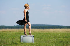 Girl with old tv at the middle of the fields Stock Image