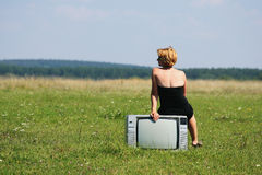 Girl with old tv at the middle of the fields Royalty Free Stock Image
