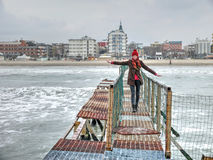 Girl on old wharf. End of winter season in Rimini, Italy - beach without people Stock Photo