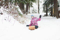 Girl on an old wooden toboggan Stock Photography