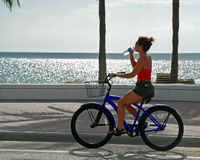 Girl On Bike Drinking Water Royalty Free Stock Images