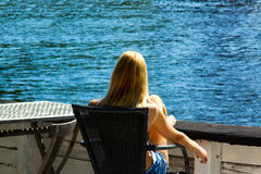 The girl onboard the ship. The girl sits in a chair onboard the yacht and looks at the sea royalty free stock images