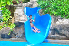 A girl ond a boy a slide. A smiling girl and boy enjoying a bouncy water  slide Royalty Free Stock Photography