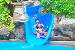A girl ond a boy a slide. A smiling girl and boy enjoying a bouncy water  slide Stock Photo
