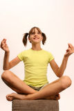 Girl onto pouffe. Girl sitting cross-legged like yogi Royalty Free Stock Photo