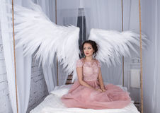 Girl with open angel wings sitting on hanging bed Stock Image