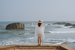 Girl with open arms looking at the ocean. Girl in a hat with open arms looking at the ocean Stock Photography