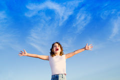 Girl open arms outdoor under blue sky Stock Images