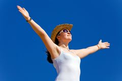 Girl with open arms over a blue sky - freedom Stock Photography