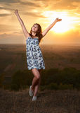 Girl open arms at sunset on plain background Royalty Free Stock Images