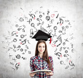 Girl with open book and education icons, concrete Stock Images