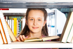 Girl with open book portrait through bookshelf Royalty Free Stock Photo