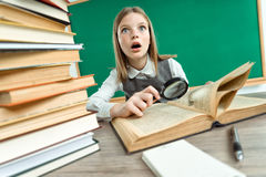 Girl open-eyed reading book with magnifier Royalty Free Stock Photo