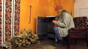 Girl open oven door bask sitting in chair by fire in rural room Royalty Free Stock Image