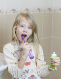 Girl with an open tube of toothpaste and an electric toothbrush. The concept of oral care Royalty Free Stock Image