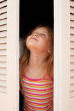 Girl in the open window Royalty Free Stock Photo