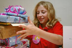 Girl opening birthday presents. Lifestyle image of child with presents Royalty Free Stock Photos